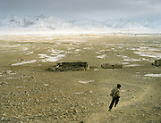 Naeem Man, young boy, running back to his house to fetch a milk bucket. In the heart ofteh Little Pamir..Campment of Sary Tash..Winter expedition through the Wakhan Corridor and into the Afghan Pamir mountains, to document the life of the Afghan Kyrgyz tribe. January/February 2008. Afghanistan
