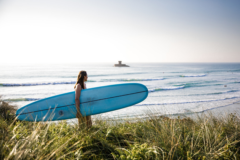 Surfer standing in the sand dunes holding her longboard at St Ouen's Bay, staring out at the sea, surf and La Rocco Tower, a landmark in Jersey, Channel Islands