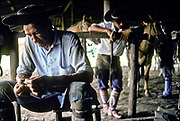 Gauchos saddling up to begin the days work on ranch, La Estrella ranch, Corrientes, Argentina