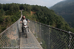 Bear Haughton on the Kusma Gyadi Bridge, the tallest (443') and one of the longest (1,128') suspension bridges in the country, on Day-7 of our Himalayan Heroes adventure riding from Tatopani to Pokhara, Nepal. Monday, November 12, 2018. Photography ©2018 Michael Lichter.
