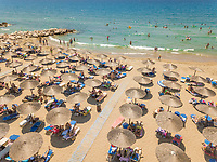 ACHAIA, GREECE - JULY 2018: Aerial view of vacationers on beach under straw parasols.