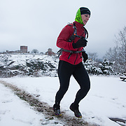 A runner makes her way up a hill from the forest below with Hammershus in the back ground.  Salomon Hammer Trail Winter Edition is a first on Bornholm and is one of the toughest routes in Denmark. The 4 runs consist of a 50 mile run, a marathon, a 1/2 marathon and 10k all run a on an approximate 25km route which includes 860 meter vertical rise on the North East coast of the Danish island Bornholm. The cut-off time for the 50mile run was 16 hours and more than a hundred runners made it to the finishing line. The last runner across the line after 50 miles  was in after 15:14:40