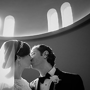 A newly married couple kisses for a black and white portrait at Holy Trinity Greek Orthodox Church in Columbia, S.C. ©Travis Bell Photography