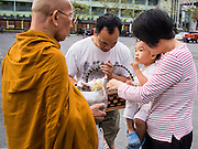 """14 FEBRUARY 2014 - BANGKOK, THAILAND:  A family presents alms to a monk on Makha Bucha Day at Wat That Thong (also called Wat Tad Tong) in Bangkok. The aims of Makha Bucha Day are: not to commit any kind of sins, do only good and purify one's mind. It is a public holiday in Cambodia, Laos, Myanmar and Thailand. Many people go to the temple to perform merit-making activities on Makha Bucha Day. The day marks four important events in Buddhism, which happened nine months after the Enlightenment of the Buddha in northern India; 1,250 disciples came to see the Buddha that evening without being summoned, all of them were Arhantas, Enlightened Ones, and all were ordained by the Buddha himself. The Buddha gave those Arhantas the principles of Buddhism, called """"The ovadhapatimokha"""". Those principles are:  1) To cease from all evil, 2) To do what is good, 3) To cleanse one's mind. The Buddha delivered an important sermon on that day which laid down the principles of the Buddhist teachings. In Thailand, this teaching has been dubbed the """"Heart of Buddhism.""""   PHOTO BY JACK KURTZ"""