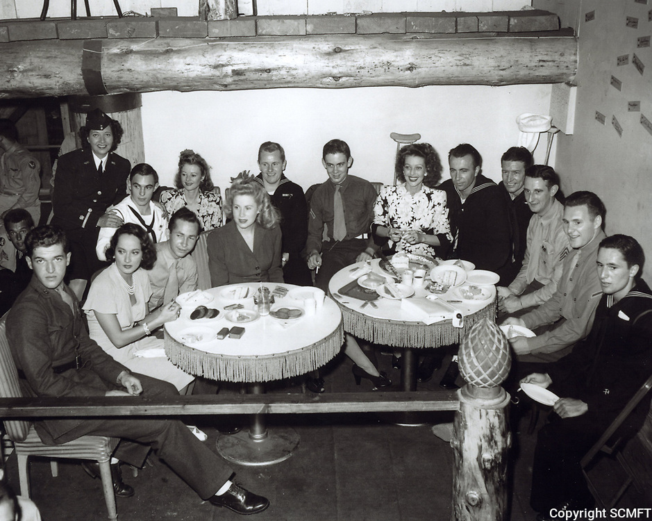 1944 (L to R) Merle Obregon, Kay Francis, Jackie White and Loretta Young sit with visitors at the Hollywood Canteen
