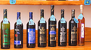 Wine bottles on a shelf for sale in the winery shop: Posip, Viva, Plavac, Potomje, Postup, Dingac and Prosek. With price tags around the necks. Matusko Winery. Potmje village, Dingac wine region, Peljesac peninsula. Matusko Winery. Dingac village and region. Peljesac peninsula. Dalmatian Coast, Croatia, Europe.