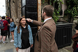 Pictured:   Security man Johnathon Bayley checks Olina before she is permitted into the garden.<br /> <br /> Pubs with beer gardens are back in action in Scotland from today.  The Pear Tree and 56 North in Edinburgh asked customers to book socially distanced tables for two-hour slots.  This is to protect staff and customers alike.  All details of booked clients are retained and temperatures taken before anybody is permitted in the Covid 19 free zone. Operations manager for the Pear Tree, Brian Dobie was keen to show customers that the bar was taking their responsibilities seriously with only table service for all food and drink.  Any walk up customers to 56 North have to provide their contact details to ensure any health issues can be traced if required.