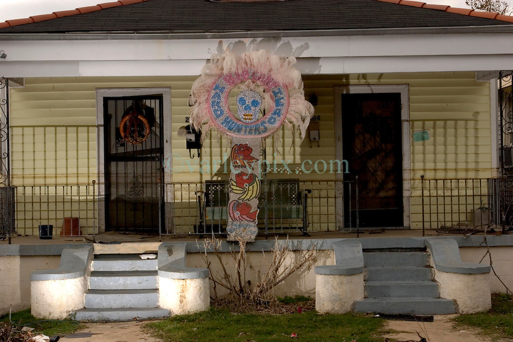 10 December, 05.  New Orleans, Louisiana.  Post Katrina aftermath.<br /> A lavish Mardi Gras Indian feathered head dress decorates the front of a devastated home in Gentilly, New Orleans east where the flood 'coffee stain' demonstrates just how high the water came.<br /> Photo; ©Charlie Varley/varleypix.com