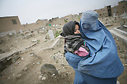 Marzia, 46, the first wife of Noor Agha, takes her youngest child, Alisa, 2, to a doctor, Kabul, Afghanistan, Thursday, March, 8, 2007. Noor Agha is a renowned kite maker who made kites for the movie makers of the best-selling novel, The Kite Runner, which will be distributed by Dreamworks and Paramount Vantage in Nov. this year. Noor Agha's wives, using their special glue, help him produce enough kites to please the clients' needs. Some of his children can also make their own kites with plastic bags and bamboo sticks. As the Afghan New Year's Day (Nawruz) approaching on March 21, the finger tips of Noor Agha's family got busier for mass production.