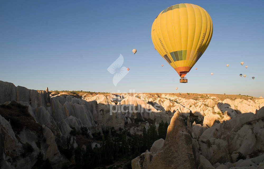 Picture by Daniel Hambury. .15/9/10..Dozens of balloons in the air during a sunrise hot hair balloon flight over the stone caves of Cappadocia, in, Turkey.