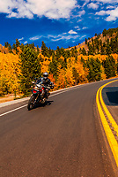 Man riding a BMW motorcycle along the Peak to Peak Highway between Nederland and Ward, Colorado USA.