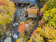 An aerial view of the grist mill at Babcock State Park shows a path decorated in fallen leaves contouring the mill and the gently flowing creek, surrounded by colorful autumnal foliage.