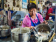 17 JANUARY 2016 - BANGKOK, THAILAND: A woman makes congee, a Thai rice porridge, in her food shop on Sukhumvit Soi 38, one of the most famous street food areas in Bangkok. The food carts and small restaurants along the street have been popular with tourists and Thais alike for more than 40 years. The family that owns the land along the soi recently decided to sell to a condominium developer and not renew the restaurant owners' leases. More than 40 restaurants and food carts will have to close. Most of the restaurants on the street closed during the summer of 2015. The remaining restaurants are supposed to close by the end of this week.          PHOTO BY JACK KURTZ