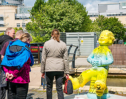 Pictured: Oor Wullie Bucket Art Trail. Leith, Edinburgh, Scotland, United Kingdom, 17 June 2019. An art trail of 200 Oor Wullie sculptures have appeared in Scottish cities overnight in a mass arts event that lasts until August 30th. The sculptures will be auctioned to raise money for Scotland's children's hospital charities. There are 5 in the Leith area, and 60 in Edinburgh altogether. Sailoor Wullie by The Leith Agency at Commercial Quay near the Scottish Government building, Victoria Quay with bemused tourists.<br /> Sally Anderson   EdinburghElitemedia.co.uk