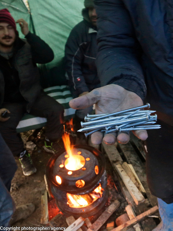 A refugee from Afghanistan shows a handful of nails that have been smuggled into the refugee camp in Grande-Synthe, northern France. Police are searching everyone who enters the informal refugee camp that has been established in a field near the port, in an effort to prevent building materials from entering the camp.