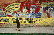 Old Communist graffiti adorns the walls of a crumbling building as an elderly lady walks past. Heroic but peeling portraits and slogans adorn the plater wall reminder passers-by of previous era when Portuguese politics were more turbulent. The Portuguese Communist Party is a major left-wing political party in Portugal. It is a Marxist-Leninist party  based upon democratic centralism. The party was founded in 1921 but made illegal after a coup in the late 1920s. The PCP played a major role in the opposition to the dictatorial regime of António de Oliveira Salazar. After the bloodless Carnation Revolution in 1974 which overthrew the 48-year regime, the 36 members of party's Central Committee had, in the aggregate, experienced more than 300 years in jail.