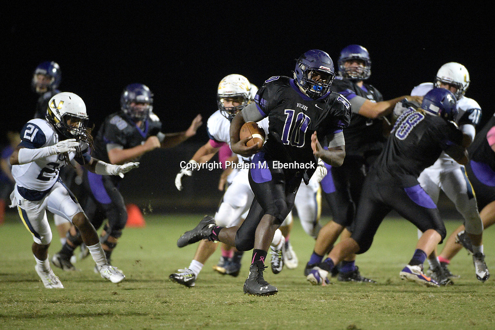 Timber Creek running back Jacques Patrick (10) rushes past University defensive back Mykal Woulard (21) for one of his five touchdowns of the first half of a high school football game in Orlando, Fla., Friday, Oct. 17, 2014. (Photo by Phelan M. Ebenhack)