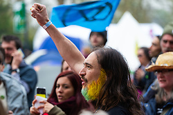 A man with a coloured beard punches the air as a meeting to discuss the day's direct action breaks up as hundreds of environmental protesters from Extinction Rebellion occupy Marble Arch, camping in the square and even on the streets, blocking access to traffic on Park Lane and Oxford Street in London's usually traffic-heavy west end. . London, April 16 2019.