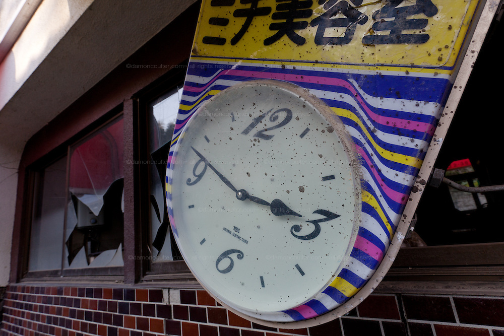 A clock outside an abandoned cafe shows the time 2:46 (when the earthquake struck) in the town of Tomioka, Futaba District of Fukushima, Japan. Monday April 29th 2013. The town was evacuated on March 12th after the March 11th 2011 earthquake and tsunami cause meltdowns at the nearby Fukushima Daichi nuclear power station. It lies well within the 20 kms exclusion zone though parts of the town have recently been opened again to allow locals to visit their property during daylight hours.