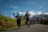 """Two men wear the baton as they run on the 20th Korrika. Erratzu (Basque Country) April 3, 2017. The """"Korrika"""" is a relay course, with a wooden baton that passes from hand to hand without interruption, organised every two years in a bid to promote the basque language. The Korrika runs over 11 days and 10 nights, crossing many Basque villages and cities, totalling some 2300 kilometres. Some people consider it an honour to carry the baton with the symbol of the Basques, """"buying"""" kilometres to support Basque language teaching. (Gari Garaialde / Bostok Photo)"""