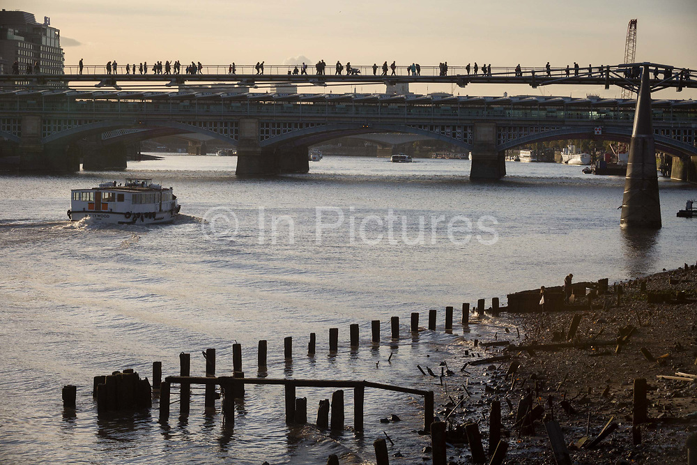 A pleasure boat passes old riverside wharf timbers and the bank of the river Thames, before continuing under pedestrians on the Millennium Bridge, on 30th October 2017, at Queenhithe in the City of London, England. Queenhithe is also the name of the ancient, but now disused, dock which derives from the Queens Dock, or Queens Quay, which was probably a Roman dock or small harbour. The dock existed during the period when the Wessex king, Alfred the Great, re-established the City of London, circa 886 AD.