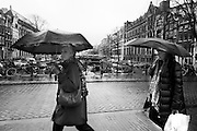 Mensen lopen onder een paraplu door de regen in Amsterdam.<br />