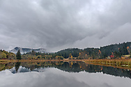Reflections of fall foliage, Mount Maxwell, and stormy clouds at Blackburn Lake on Salt Spring Island, British Columbia, Canada
