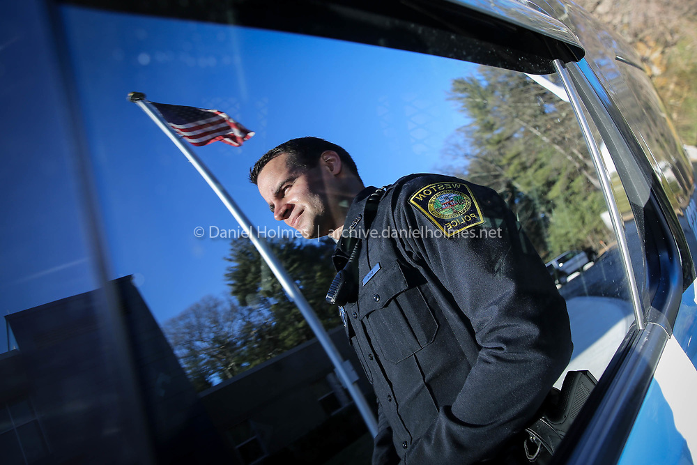 (2/12/18, WESTON, MA) Officer Henry Gula poses for a photo at the Weston Police Station on Monday. Officer Gula was born and raised in Weston, and is Weston's newest police officer. [Daily News and Wicked Local Photo/Dan Holmes]