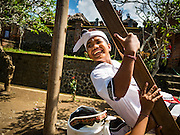 22 JULY 2016 - TENGANAN DUAH TUKAD, BALI, INDONESIA: A boy plays on human powered ferris wheel and swing before the Pandanus fights in the Tenganan Duah Tukad village on Bali. The ritual Pandanus fights are dedicated to Hindu Lord Indra. Men engage in ritual combat with spiky pandamus leaves and rattan shields. They usually end up leaving bloody scratches on the combatants' backs. The young girls from the community wear their best outfits to watch the fights. The fights have been traced to traditional Balinese beliefs from the 14th century CE. The fights are annual events in the Balinese year, which is 210 days long, or about every seven months in the Gregorian calendar.    PHOTO BY JACK KURTZ