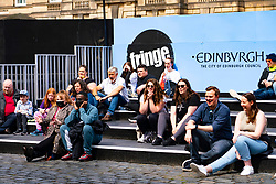 Edinburgh, Scotland, UK. 6th August  2021.  Images from the Royal Mile in Edinburgh Old Town on the opening day of the Edinburgh Fringe Festival 2021.  The festival looks very different from two years ago . Very few street performance spaces are permitted and far fewer tourists are evident. Also a high police visibility, there are more police officers than performers on the street, is in marked contrast to previous years. Pic; Audience watch performer in screened off performance space at St Gile Cathedral.  Iain Masterton/Alamy Live news.