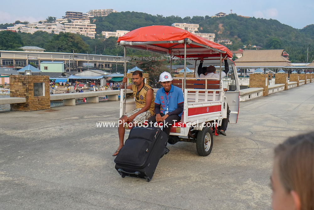 An auto rickshaw is carrying passengers at the Big Buddha port in Koh Samui, Thailand