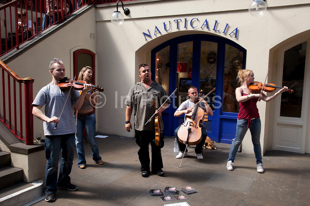 Busking classical musicians play fort an audience of onlookers at Covent Garden, Central London. The band play opera with a humorous twist in their performance.
