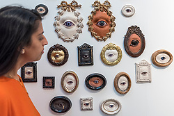 © Licensed to London News Pictures. 16/01/2018. LONDON, UK.  A staff member views an artwork made of sculptured eyes at the James Freeman Gallery stand.  Preview day of the 30th anniversary of the London Art Fair.  The fair launches the international art calendar with modern and contemporary art from leading galleries around the world and is taking place at the Business Design Centre, Islington from 17 to 21 January 2018.   Photo credit: Stephen Chung/LNP