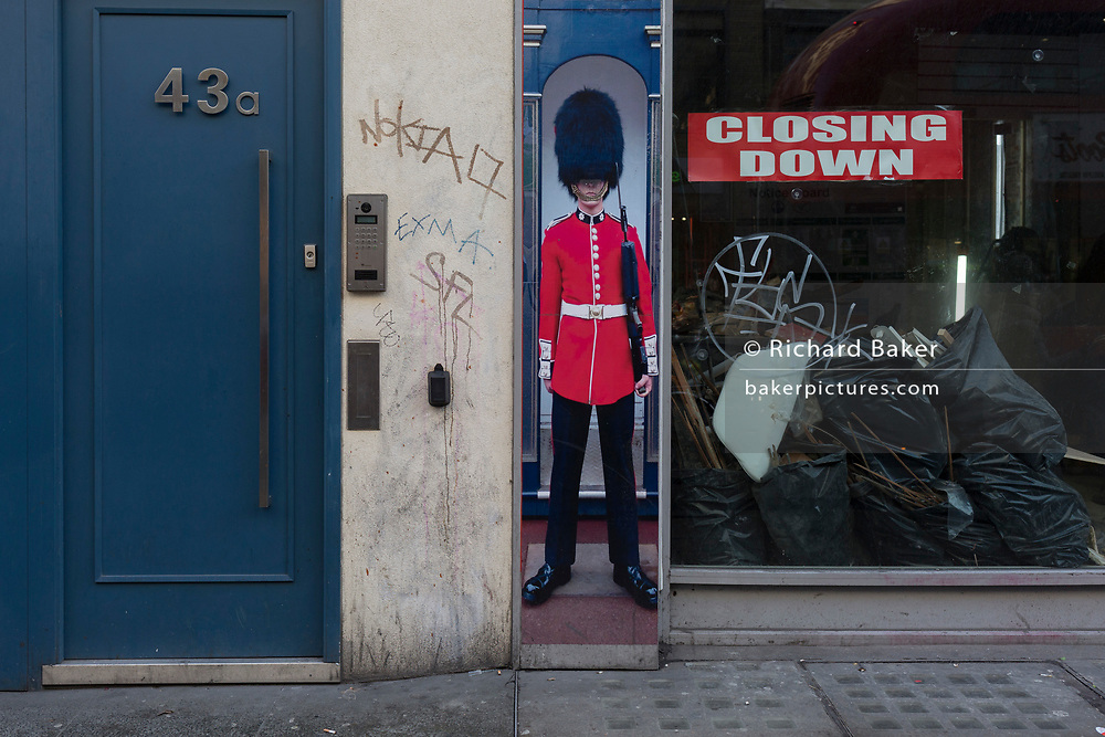 The squashed perspective of a grenadier guardsman standing as sentry next to a doorway and a closed down business - a metaphor for Brexit, on Oxford Street, on 12th December 2017, in London England.