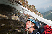 Valerie Wall drinks water dripping off snow at the base of Mount Triumph, North Cascades National Park, Washington.