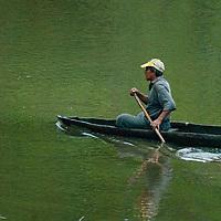 A Peruvian Amazon Indian paddles his canoe on the Yanayacu River.