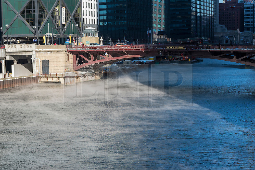 © Licensed to London News Pictures. 15/12/2016. Chicago, USA. The city of Chicago suffers the first severe cold of the year with daytime temperatures of -5F or -15C recorded. The air temperature is so cold causing steam to rise from the relatively warmer Chicago River.  Photo credit : Stephen Chung/LNP