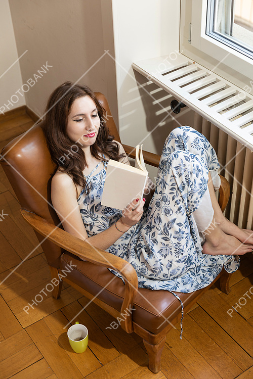 Young beautiful girl with long dress is sitting on an old armchair and reading a book