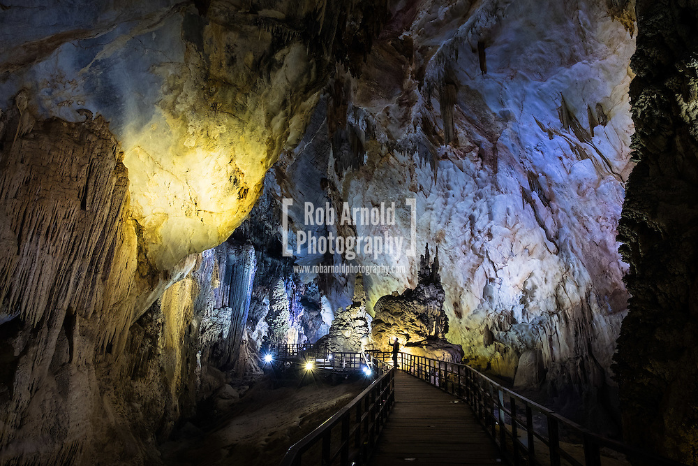 A woman takes a photograph within Paradise Cave in Phong Nha National Park, Vietnam