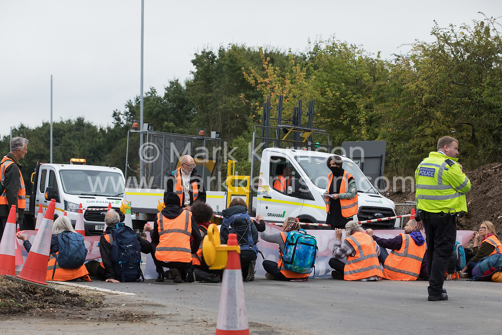 Enfield, UK. 15th September, 2021. Insulate Britain climate activists block for a second time a slip road from the M25 at Junction 25 as part of a campaign intended to push the UK government to make significant legislative change to start lowering emissions. The activists, who wrote to Prime Minister Boris Johnson on 13th August, are demanding that the government immediately promises both to fully fund and ensure the insulation of all social housing in Britain by 2025 and to produce within four months a legally binding national plan to fully fund and ensure the full low-energy and low-carbon whole-house retrofit, with no externalised costs, of all homes in Britain by 2030 as part of a just transition to full decarbonisation of all parts of society and the economy. Credit: Mark Kerrison