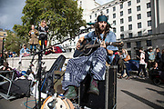 Extinction Rebellion climate change activist and musician Cam Cole plays guitar as sites around Westminster are blocked on 8th October 2019 in London, England, United Kingdom. Extinction Rebellion is a climate group started in 2018 and has gained a huge following of people committed to peaceful protests. These protests are highlighting that the government is not doing enough to avoid catastrophic climate change and to demand the government take radical action to save the planet.