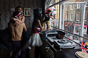 Soho celebrates the Queen's Diamnond Jubilee weeks before the Olympics come to London. A topless man dances with a girl whose legs are wrapped around his waste, his broad chest and muscled upper-body to the crowds below who are dancing to the loud music pumped out through open windows on this summer's afternoon in the heart of Soho. The DJ is being filmed by a cameraman and union jack flags are strung up along the sill. The UK gears enjoys a weekend and summer of patriotic fervour as their monarch celebrates 60 years on the throne. Across Britain, flags and Union Jack bunting adorn towns and villages.