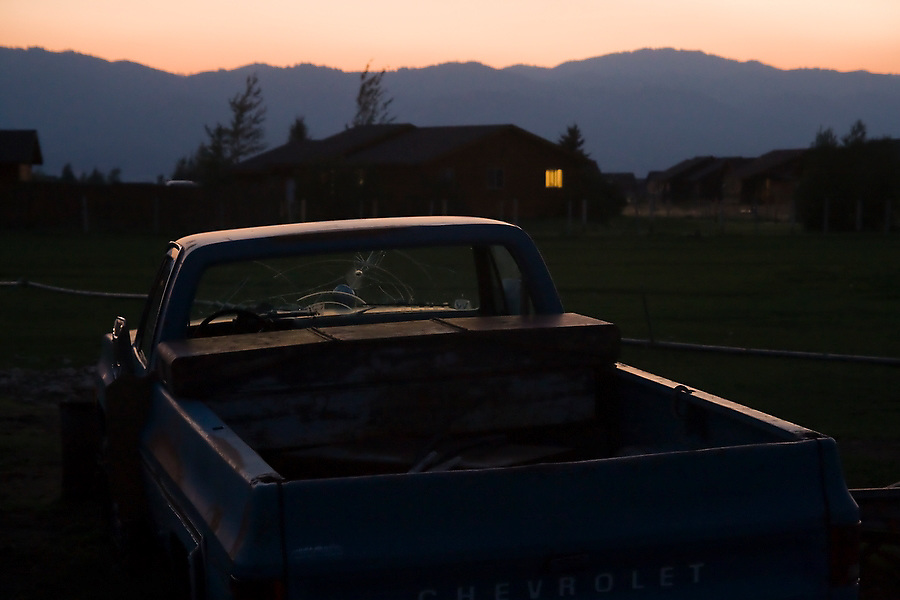 A broken pickup truck lies in a field at sunset as a small window glows from the farm house in Victor, Idaho.