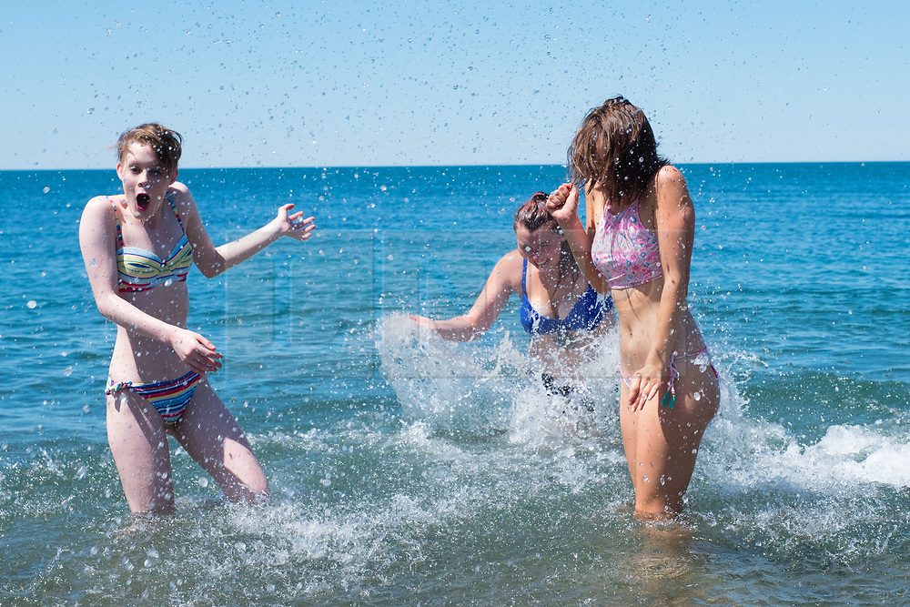 © Licensed to London News Pictures. 29/06/2018. Aberystwyth, UK. Dance Students Kai Sales and Annie Williams cool down in the water after an end of term performance, as people flock to the seaside in Aberystwyth as the scorchingly hot  and very dry weather continues to dominate the UK Photo credit: Keith Morris/LNP