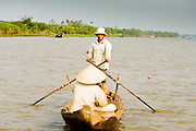 12 MARCH 2006 - CAI BE, TIEN GIANG, VIETNAM: A man rows a small boat to Cai Be in the Mekong River delta. The Mekong is the lifeblood of southern Vietnam. It is the country's rice bowl and has enabled Vietnam to become the second leading rice exporting country in the world (after Thailand). The Mekong delta also carries commercial and passenger traffic throughout the region.  Photo by Jack Kurtz