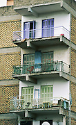 Three stories of highrise balconies have purple and green shuttered doors in Athens, Greece, Europe.