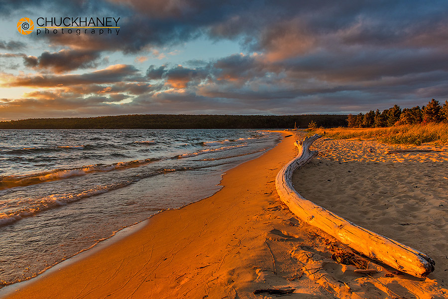 Dramatic sunset light on weathered driftwood at Sand Point in Pictured Rocks National Lakeshore, Michigan, USA