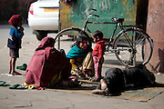 A family lives homeless at the train station in Jaipur, the father sleeps on the ground as the mother tends to one of her children.  Children, some who have run away from their families, find themselves living homeless on the train tracks waititng for the next train to arrive at the train station in Jaipur, India.  Once the train arrives they raid the train looking for plastic bottles that they can then sell.  Most will make about $1.50/day but spend most of it on glue which they are most addicted to.