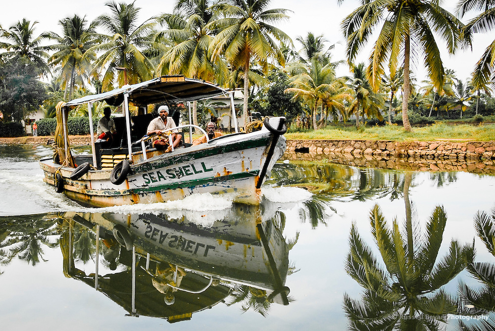 A boat navigates the busy Kerela backwaters in southern India