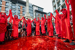 """© Licensed to London News Pictures. 27/08/2021. LONDON, UK.  Red Rebels in their costumes join climate activists from Extinction Rebellion protesting in Paternoster Square in The City of London.  The event is part of the 'Impossible Rebellion' protest to """"target the root cause of the climate and ecological crisis"""" and are ongoing for two weeks until the Government agrees to stop all new fossil fuel investments.  Photo credit: Stephen Chung/LNP"""